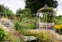 Gravel garden with naturalistic pond, metal gazebo and late season perennials and grasses in rural Nottinghamshire in September.
