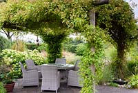 Rose covered arbour over a dining area in a rural garden with bubble millstone water feature in the foreground and grasses and hydrangea behind.