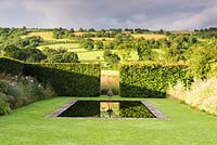 The bronze garden, with a reflecting pool at its centre with hedging.