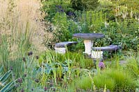 A pondside table and benches at Bluebell Cottage Gardens, Cheshire. Planting includes Hostas, Astilbes and Veronicastrums.
