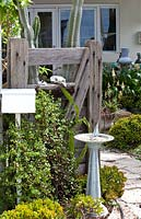 Garden gate made from recycled timber with a freestanding letterbox a sundial with a yacht gnomon in a dry tolerant garden planted with a variety of succulents featuring a Jade Plant.
