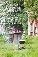 Rustic wooden table and chairs, table set for breakfast - fire place with cooking facilities in background.