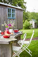 Rustic table set for breakfast with view to shepherds hut