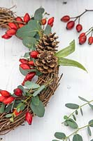 Detail of wicker wreath with rosehips, pine cones and Eucalyptus foliage