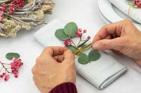 Woman decorating a napkin with rowan berries and Eucalyptus.