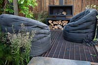Seating area in the contemporary garden using recycled materials and a dark colour palette - the Hairy Gardener's Garden at BBC Gardener's World Live 2017