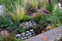 'Find Yourself Lost in the Moment' garden - RHS Chatsworth Flower Show 2019 - view of path showing pebbles surrounded by low growing plants.