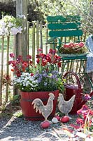 Wooden hens and coloured eggs near a red wooden bucket planted with Erysimum 'Winter Passion' and 'Poem Lavender' - Wallflower - and Iberis sempervirens 'Candy Ice' - Candytuft s