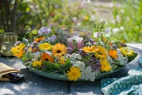 Candle in wreath of marigold flowers, sage, oregano flowers as table decoration