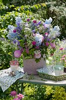 Bouquet of delphiniums, bluebells, dahlias, clove orchid, catnip, aster on a table in the garden