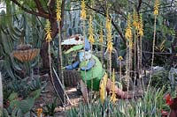 Private desert cactus and succulent garden with rustic painted iron garden sculpture of  dinosaur and planted with Agave, Yucca and Cacti