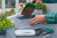 Woman using plastic scoop to add compost to container