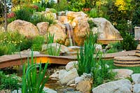 A natural looking stream and waterfall constructed from large boulders and small rocks, next to a small timber deck, interplanted with a variety of flowering and strappy leaved plants, featuring a low arched timber bridge and a small lawn area with circular seagrass cushions.