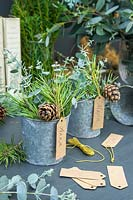 Name tags hung from metal pots filled with mixed green foliage and pine cones