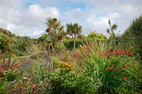 The Beth Chatto Garden with glass domed bird table, grasses, papavers, Phormium, Cordyline and Crocosmia