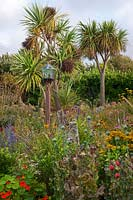 The Beth Chatto Garden with glass domed bird table, grasses, Rudbeckias, Perovskia, Nasturtiums, and Cordyline