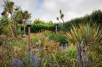 The Beth Chatto Garden with glass domed bird table, grasses, Echinacea, Rudbeckia, Perovskia, Phormium, Cordyline and Crocosmia