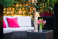 Outdoor seating area with pink cushions and vase of Tulipa - Tulip - on table, foliage backdrop on wooden trellis