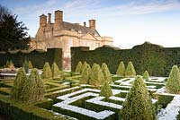 A knot garden of clipped Buxus - Box - with variegated Box pyramids, surrounded by formal hedge with house beyond