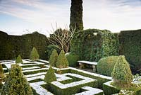 A knot garden of clipped Buxus - Box - with variegated Box pyramids, enclosed in formal hedge with Hedera - Ivy - covered arbour over stone bench