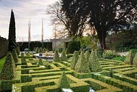 A knot garden of clipped Buxus - Box - with variegated Box pyramids and a central basketwork pond