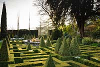 View over knot garden of clipped Buxus - Box - with variegated Box pyramids and a central basket pond