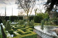 Raised pond with basketwork pattern surrounded by a knot garden of clipped Buxus - Box - with variegated Box pyramids