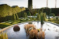 View over pond with planting towards knot garden of clipped Buxus - Box - with variegated Box pyramids and formal hedge