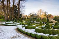 Parterre of clipped Buxus - Box, plus Taxus - Yew - columns and mophead Prunus lusitanica 'Myrtifolia', views of garden beyond