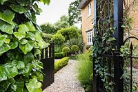 Gate framed with ivy into a contemporary cottage front garden