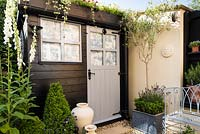 Deluxe garden shed framed by standard olive, ceramic jars, clipped box and white foxgloves