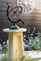 Sundial in contemporary cottage garden with clock and scabious in background
