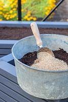 Metal tub with compost and vermiculite ready for mixing with scoop, seed sowing mix