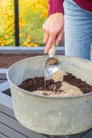 Using a scoop to mix compost and vermiculite together to make a seed compost