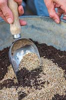 Using a scoop to mix compost and vermiculite to make a seed compost