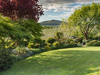 View across lawn to mixed border with views to an apple orchard and hills beyond