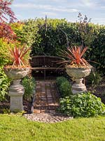 Path of recycled bricks leads to wooden bench under metal arbour, two urns o plinths either side of the path planted with Cordyline australis 'Torbay Dazzler'