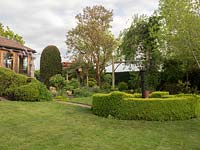 View across lawn with vintage pump enclosed with Buxus - Box - edging towards mixed beds with trees