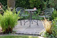 Circular patio with table and chairs and beds planted with ferns, trees and shrubs