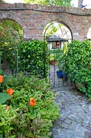 Wrought iron arched garden gate in a red brick wall with cobbled garden path leading to separate garden rooms.