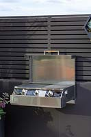 A small three burner barbecue mounted and a wall in a rooftop, patio garden.