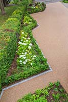 View from above of angular borders edged with cobbled granite and planted with woodland plants such as Hydrangea and Buxus
