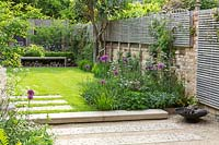 A contemporary city garden with borders of alliums and cow parsley, lawn, bench and raised wooden screen for extra privacy.