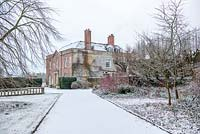Snow covered drive leading to Yarlington House with bright red Cornus stems