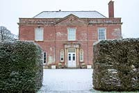 The front entrance of Yarlington House with clipped yew hedges in a dusting of snow