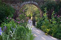 Gravel pathway through gate set in arch of old brick boundary wall by flowering summer borders.