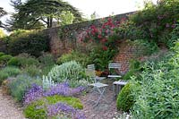 Table and chairs on brick patio by border of Campanula, Echinops, Stachys and red Rosa climbing up brick wall.
