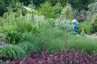 View over mixed border with grasses to Europa riding Zeus sculpture - The World Garden, Lullingstone Castle, Kent, UK.