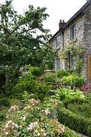 Small cottage garden with Roses in low  Buxus parterre and rasied bed of herbs next to stone house