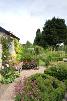 Small country cottage garden with parterre and gravel path leading to bench